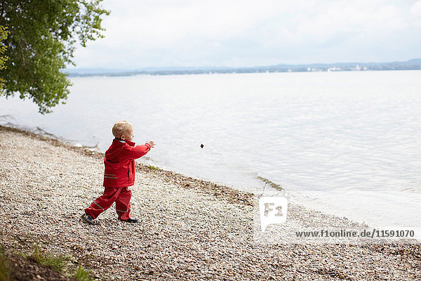 Boy tossing rocks into lake