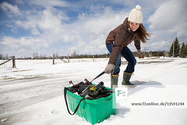 Woman dragging recycling in snow
