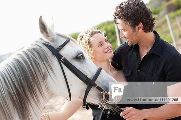 couple smiling holding horse