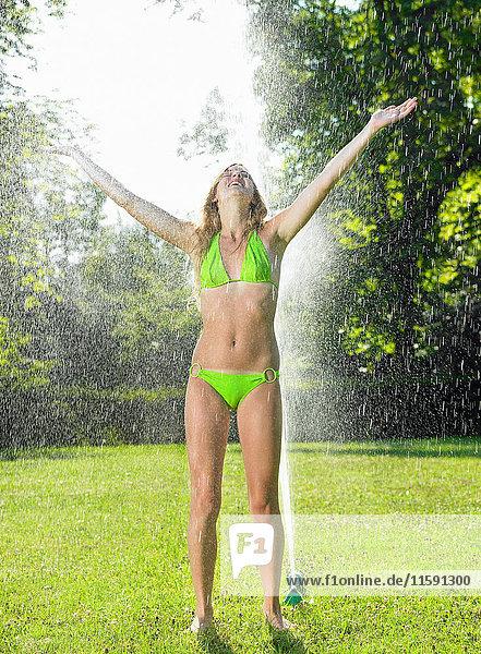 Mädchen unter einem Wasserstrahl