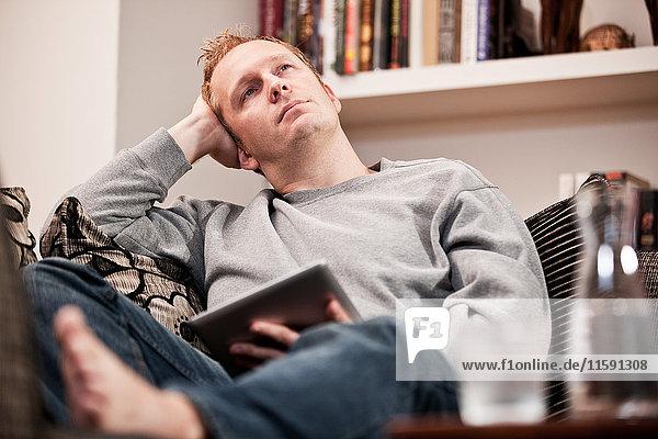 Mittlerer Erwachsener Mann mit digitalem Tablett auf dem Sofa
