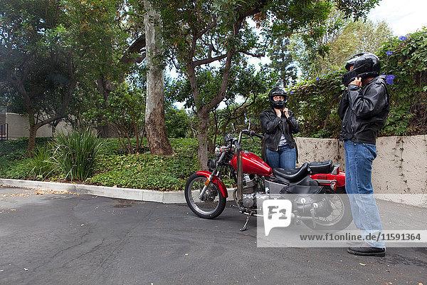Älteres lesbisches Paar bereitet sich auf Motorradfahren vor