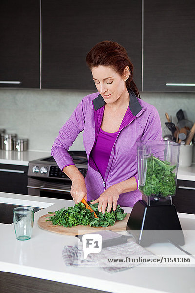 Mature woman making vegetable juice