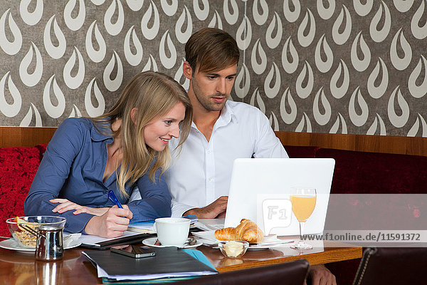 Couple studying with laptop in cafe
