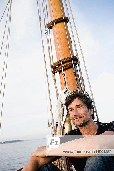 Mann sitzt an Deck eines Segelbootes