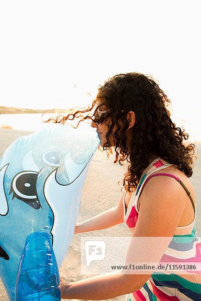 Frau küsst aufblasbares Spielzeug am Strand