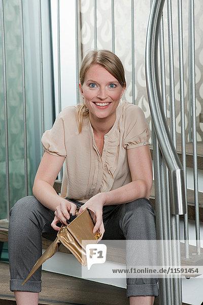 Frau hält ihre Handtasche auf der Treppe