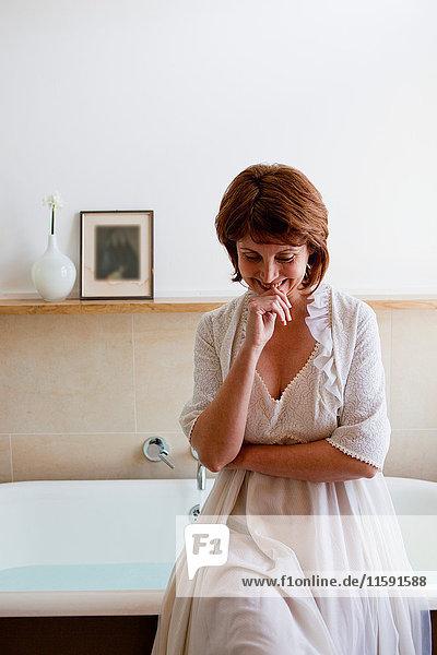 Frau an der Badewanne sitzend