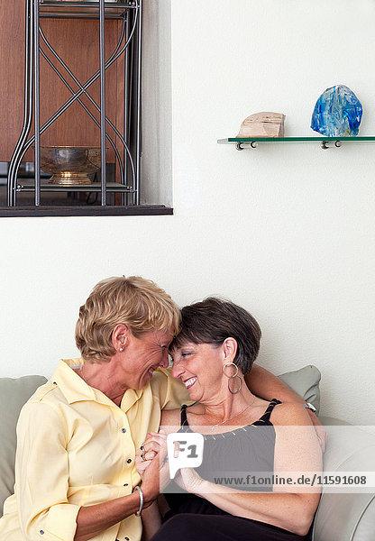 Ein reifes lesbisches Paar  das sich auf dem Sofa umarmt