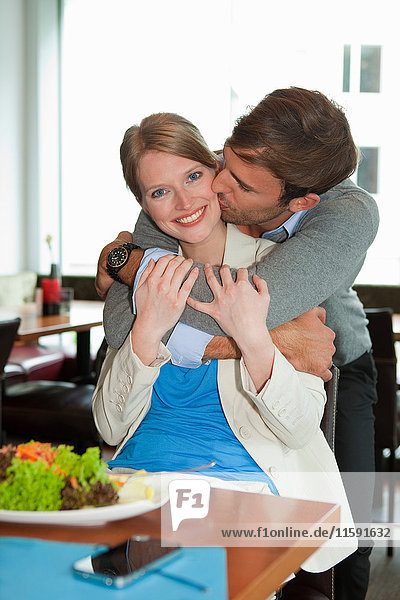Man kissing girlfriend at lunch
