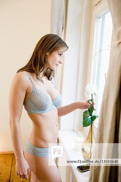 Junge Frau  die aus einem Fenster schaut