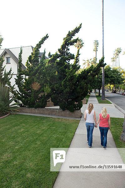Junges lesbisches Paar beim Gehen auf dem Bürgersteig  Rückansicht
