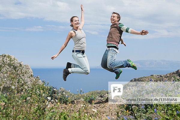 junges Paar springt in die Luft