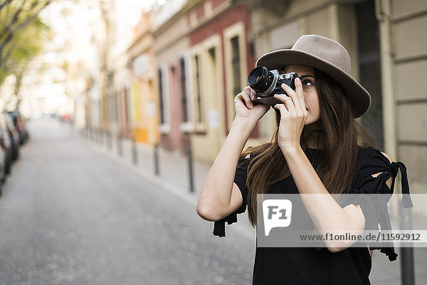 Young woman taking pictures with camera outdoors