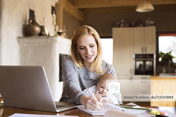Mutter mit Kind zu Hause mit Laptop und Notizen