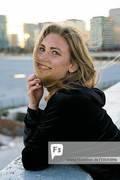 Spanien  Barcelona  Porträt einer lächelnden jungen Frau mit wehendem Haar