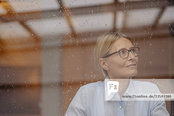 Geschäftsfrau hinter verregneter Fensterscheibe schaut weg