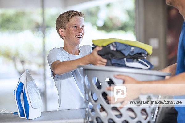 Junge hilft Vater bei der Arbeit mit dem Wäschekorb