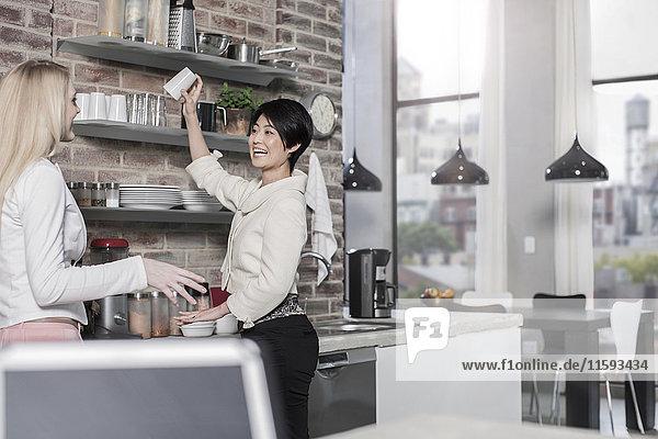 Zwei Freundinnen in moderner Küche mit Blick auf die Stadt