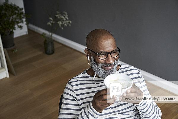 Erwachsener Mann mit Kopfhörern beim Kaffeetrinken