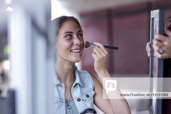 Mädchen  das Make-up aufträgt  während die Mutter den Spiegel hält. Mädchen, das Make-up aufträgt, während die Mutter den Spiegel hält.