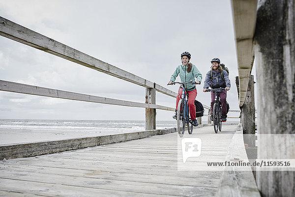Deutschland  Schleswig-Holstein  St. Peter-Ording  Paar Radfahren am Steg am Strand