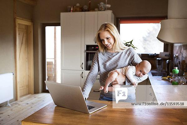 Lächelnde Mutter mit Baby in der Küche mit Laptop