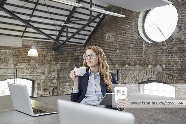 Geschäftsfrau mit Tasse Kaffee und Tablette am Tisch im Loft