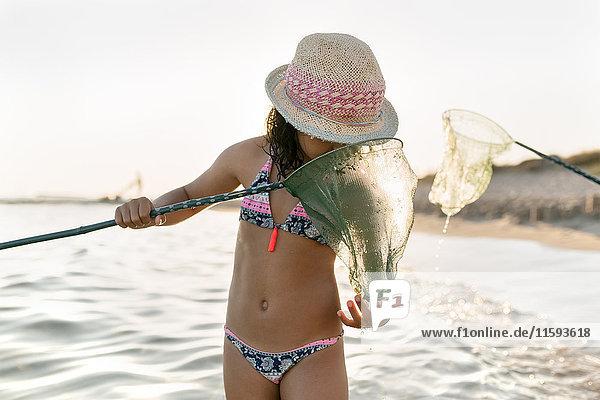 Spanien  Menorca  Mädchen mit Netz am Strand
