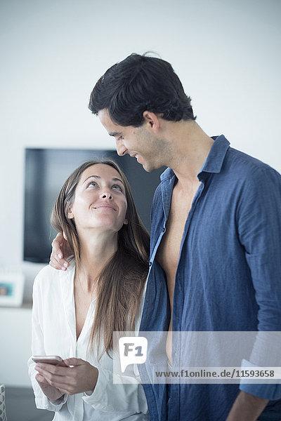 Lächelndes junges Paar verliebt in das Handy zu Hause