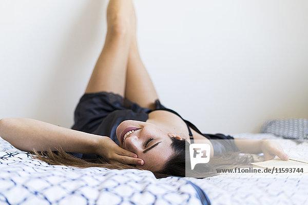 Fröhliche junge Frau im Bademantel auf dem Bett liegend