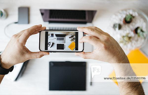 Mann fotografiert seinen Schreibtisch mit Smartphone  Draufsicht