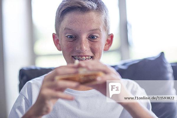 Junge hält Sandwich in der Hand