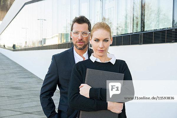 Porträt eines selbstbewussten Geschäftsmannes und einer selbstbewussten Frau im Freien