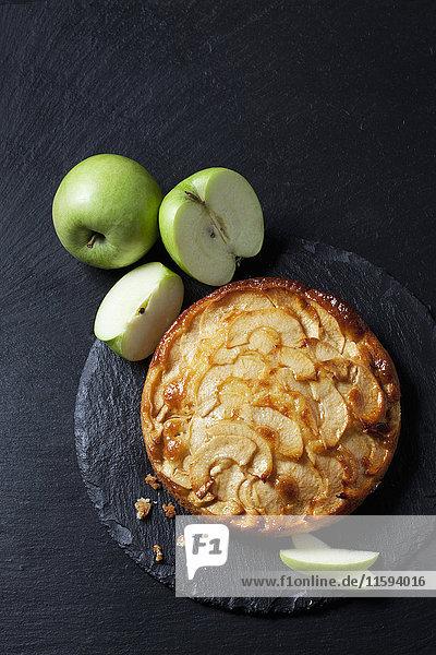 Apfelkuchen und grüne Äpfel auf Schieferplatte Apfelkuchen und grüne Äpfel auf Schieferplatte