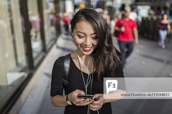 USA  New York City  Manhattan  young woman listening music with earphones while looking at cell phone