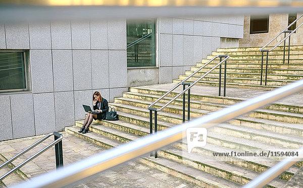 Geschäftsfrau auf der Treppe sitzend  mit Laptop