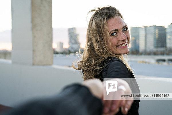 Spanien  Barcelona  Porträt einer glücklichen jungen Frau  die die Hand hält