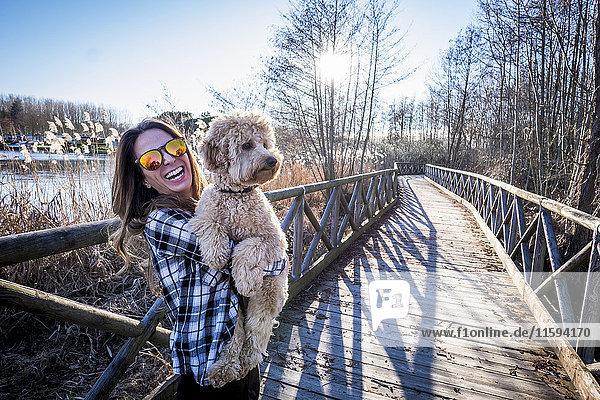 Frau steht auf der Brücke und hält ihren Hund.