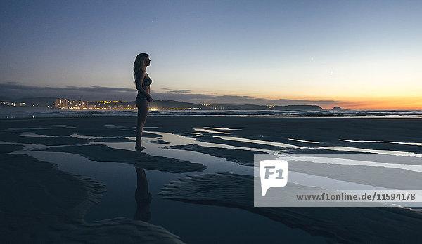 Junge Frau beobachtet den Sonnenuntergang am Strand