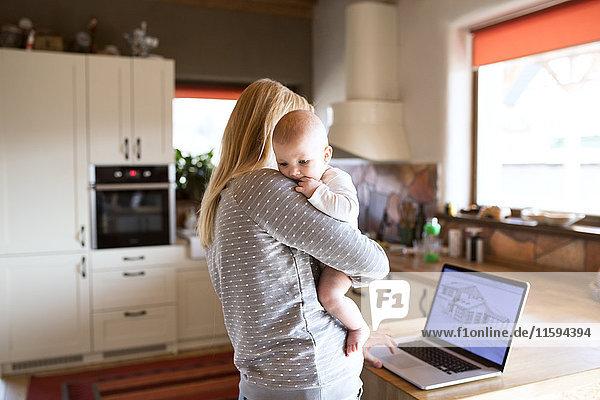 Mutter mit Baby zu Hause mit Blick auf das Haus auf dem Laptop-Bildschirm