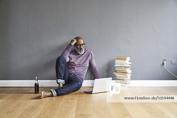 Erwachsener Mann auf dem Boden sitzend  mit Laptop