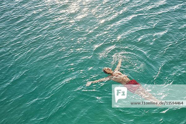Reifer Mann im smaragdgrünen Wasser schwimmend