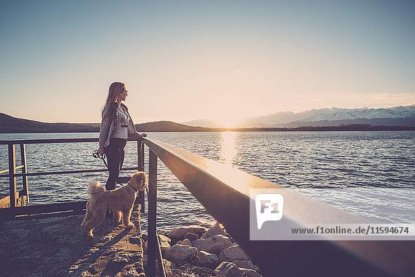Frau am See bei Sonnenuntergang mit ihrem Hund Frau am See bei Sonnenuntergang mit ihrem Hund