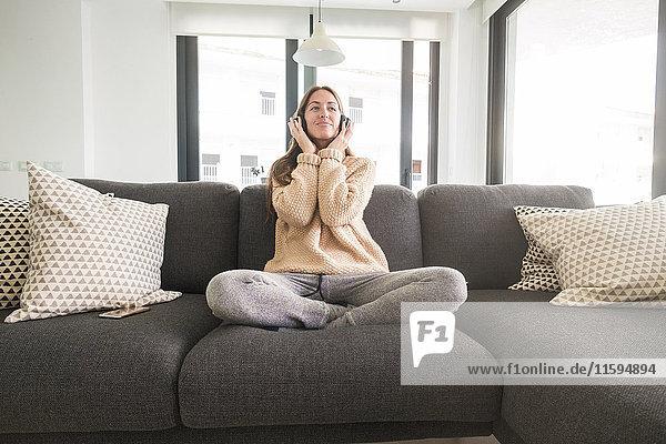 Lächelnde junge Frau  die zu Hause Musik hört.