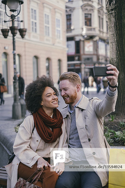 Ein glückliches Paar  das einen Selfie in der Stadt nimmt.