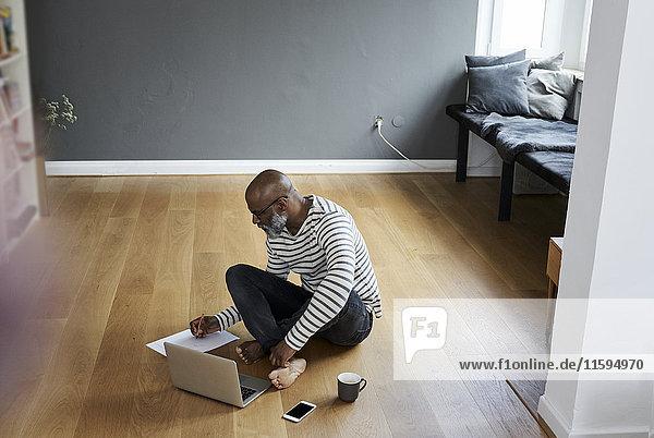 Erwachsener Mann auf dem Boden sitzend  am Laptop arbeitend