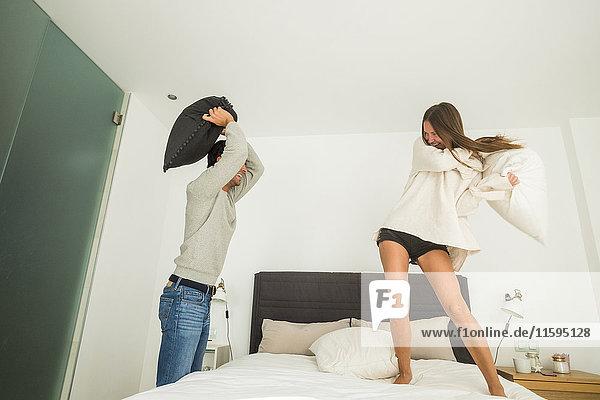 Verspieltes junges Paar bei einer Kissenschlacht zu Hause