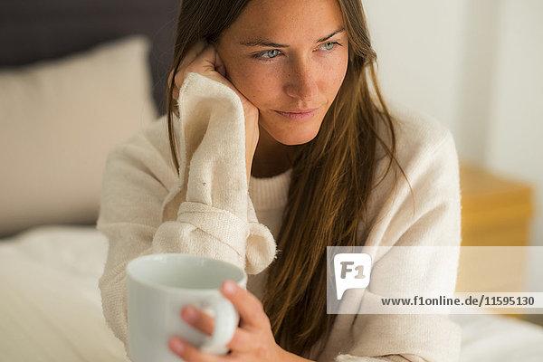 Junge Frau auf dem Bett sitzend mit einer Tasse Kaffee