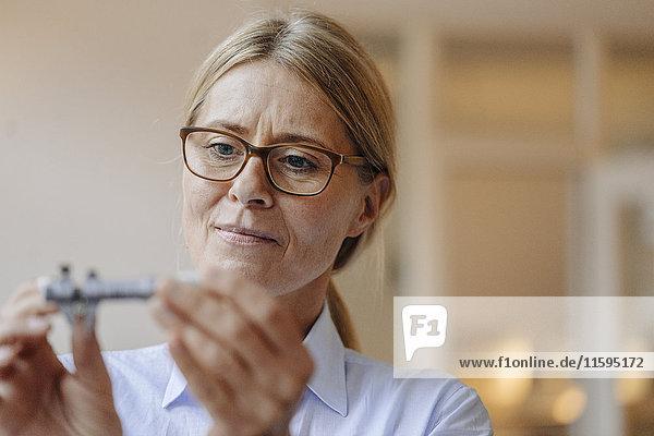 Porträt einer Geschäftsfrau  die etwas hält und anschaut